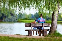 Vater und Sohn auf der Bank nahe dem See Stockfotos