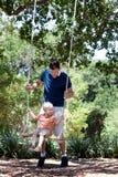 Vater und Sohn auf einem Schwingen Stockfotografie