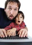 Vater und Sohn auf Laptop lizenzfreie stockfotografie