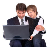 Vater und Sohn auf Laptop Stockfotos