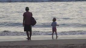 Vater und Sohn auf Strand bei Sonnenuntergang stock footage