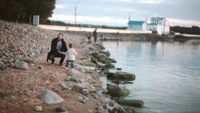 Vater und Sohn auf Strandhändchenhalten und Gehen entlang das Ufer bei Sonnenuntergang Mädchen, das läuft, um zu bemannen Vater u stock footage