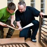 Vater und Sohn bauen Krippe zusammen Lizenzfreie Stockbilder