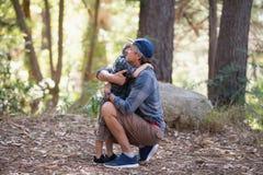 Vater und Sohn beim Wandern im Wald umfassen Stockbilder