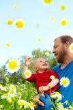 Vater und Sohn in den Blumen Stockbilder