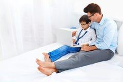 Vater und Sohn in den Brillen unter Verwendung des Notizbuches Stockfotos