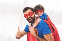 Vater und Sohn in den roten und blauen Klagen von Superhelden Auf ihren Gesichtern sind Masken und sie sind in den Regenmänteln Lizenzfreies Stockbild