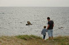 Vater und Sohn an der Küste Stockbilder