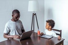 Vater und Sohn, der Laptop und Tablette verwendet Stockfotografie