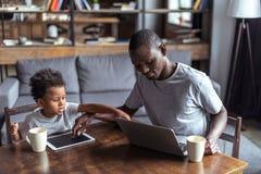 Vater und Sohn, der Laptop und Tablette verwendet Stockfotos