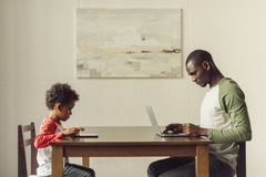 Vater und Sohn, der Laptop und Tablette verwendet Lizenzfreies Stockbild