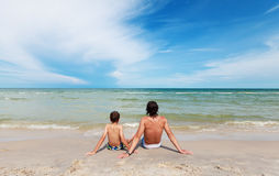 Vater und Sohn, die auf dem sandigen Strand sitzen. Stockbilder