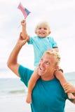 Vater und Sohn, die auf dem Strand spielen Lizenzfreies Stockbild