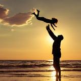 Vater und Sohn, die auf dem Strand zur Sonnenuntergangzeit spielen Stockbilder