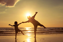 Vater und Sohn, die auf dem Strand zur Sonnenuntergangzeit spielen Lizenzfreie Stockfotografie