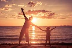 Vater und Sohn, die auf dem Strand zur Sonnenuntergangzeit spielen Lizenzfreie Stockfotos