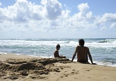 Vater und Sohn, die auf dem Strand zur Sonnenuntergangzeit spielen Konzept der freundlichen Familie stockfoto