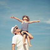 Vater und Sohn, die auf dem Strand zur Tageszeit spielen Stockfotografie