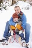 Vater und Sohn, die auf Schlitten sitzen Stockfotos