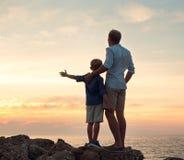Vater und Sohn, die auf Sonnenuntergang dem Meer betrachten Lizenzfreie Stockfotografie