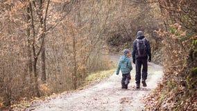 Vater und Sohn, die auf Waldweg gehen Lizenzfreie Stockfotos