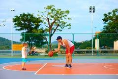 Vater und Sohn, die Basketball auf Sportplatz spielen Stockfoto