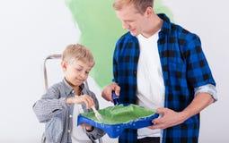 Vater und Sohn, die das Haus neu streichen Stockbilder