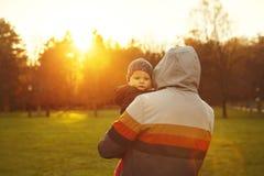 Vater und Sohn, die den Sonnenuntergang in der Herbstnatur aufpassen Stockfotos