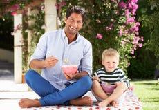 Vater und Sohn, die draußen Frühstückskost aus Getreide genießen Lizenzfreie Stockfotos