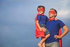Vater und Sohn, die draußen Superhelden zur Tageszeit spielen Stockfoto