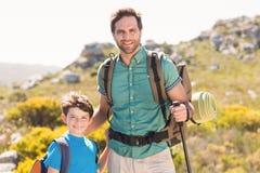 Vater und Sohn, die durch Berge wandern Stockbilder
