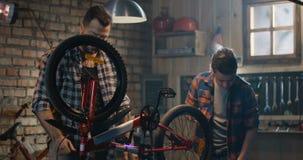Vater und Sohn, die ein Fahrrad in einer Garage reparieren stock video