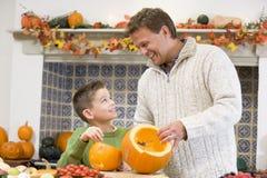 Vater und Sohn, die ein punpkin für Halloween schnitzen