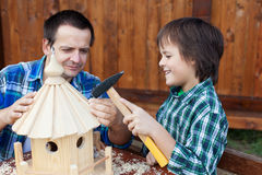 Vater und Sohn, die ein Vogelhaus oder -zufuhr errichten Stockfotografie