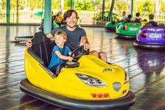 Vater und Sohn, die eine Fahrt im Autoskooter am Vergnügungspark haben stockbilder