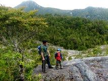 Vater und Sohn, die einen Berg klettern Stockfoto