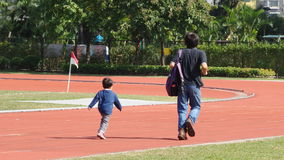 Vater und Sohn, die einen laufenden Wettbewerb auf Sportplatz haben Lizenzfreie Stockfotografie