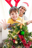 Vater und Sohn, die einen Weihnachtsbaum verzieren lizenzfreies stockfoto