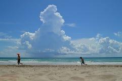 Vater und Sohn, die entlang den Strand laufen Stockfotos