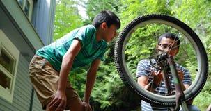Vater und Sohn, die Fahrrad 4k reparieren stock video footage