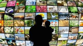 Vater und Sohn, die Fernsehbildschirme betrachten Stockfotos
