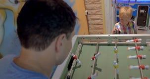 Vater und Sohn, die Foosball im Säulengang spielen stock video
