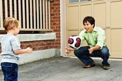 Vater und Sohn, die Fußball spielen stockfotos