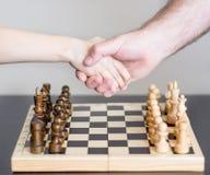 Vater und Sohn, die Hände vor dem Spiel des Schachs rütteln stockfotografie
