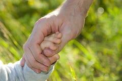 Vater und Sohn, die Hand in Hand halten Stockfotografie