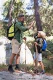 Vater und Sohn, die Hoch fünf beim Wandern im Wald geben Stockfotos
