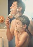 Vater und Sohn, die im Badezimmer sich rasieren Stockfoto