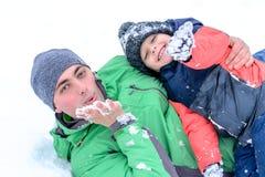 Vater und Sohn, die im Schnee spielen Lizenzfreie Stockfotografie