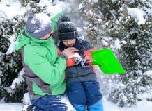 Vater und Sohn, die im Schnee spielen Stockfotos