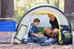 Vater und Sohn, die innerhalb des Zeltes beim Wandern im Wald sitzen Lizenzfreie Stockbilder